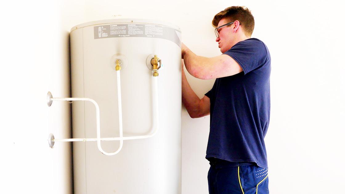 Plumber repairing hot water system - Gold Coast